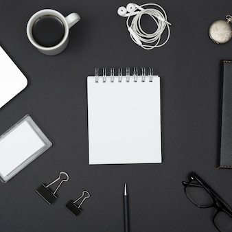 Vista elevada del auricular; taza de café; clips de papel; lente; con la libreta blanca en blanco dispuesta en fondo negro
