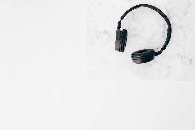 Una vista elevada de auriculares negros en el escritorio sobre fondo blanco