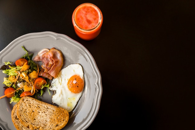 Una vista elevada de batido rojo en frasco de vidrio con pan tostado; ensalada; tocino y huevo frito en placa gris sobre fondo negro