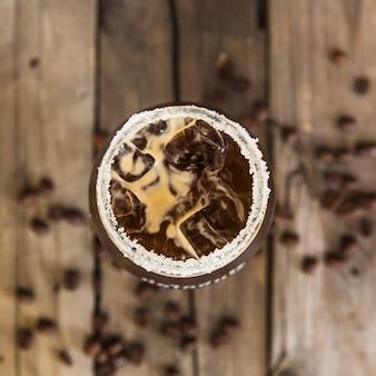 Vista elevada de la bebida de café fresco en el escritorio de madera