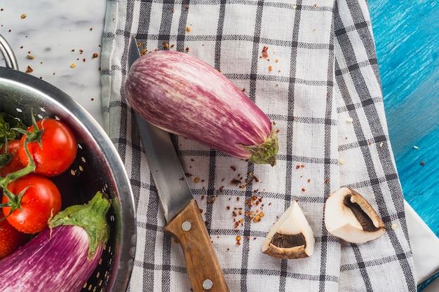Vista elevada de berenjena; seta; chili flake y cuchillo en tela de patrón a cuadros