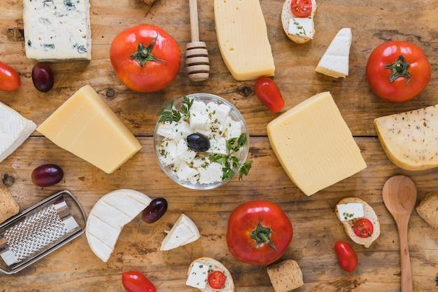 Una vista elevada de bloques de queso con tomates; uvas en mesa de madera