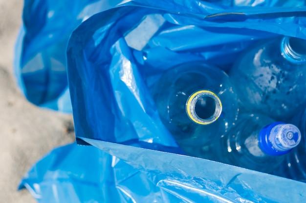 Vista elevada de la bolsa de basura azul de botellas de plástico de desecho