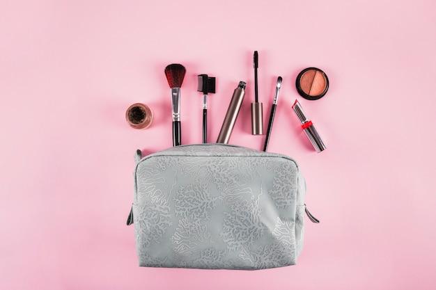 Vista elevada de la bolsa de cosméticos que contiene lápiz labial; máscara; delineador de ojos y pinceles sobre fondo rosa