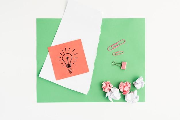 Vista elevada de bombilla dibujada y papel arrugado con clip sobre papel de tarjeta verde