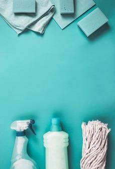 Vista elevada de botellas de plástico, cabeza de trapeador, esponja y servilleta sobre fondo turquesa