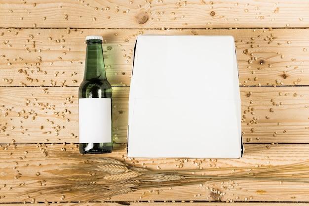 Vista elevada de la caja de cartón; botella de cerveza y espigas de trigo sobre fondo de madera