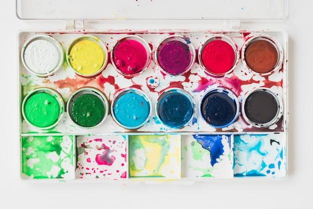 Vista elevada de una caja de pintura de color de agua húmeda desordenada