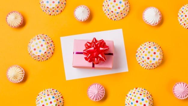 Una vista elevada de la caja de regalo en papel blanco con formas de pastel de papel de lunares y aalaw sobre fondo amarillo