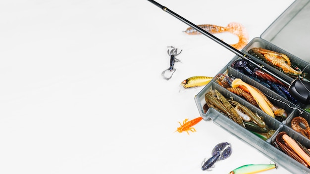 Vista elevada de la caja de señuelos con caña de pescar sobre fondo blanco