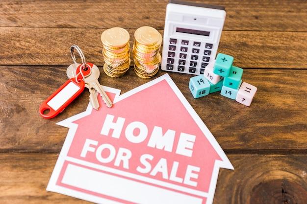 Vista elevada de la calculadora, bloques de matemáticas, monedas apiladas y llave con el icono de casa en venta
