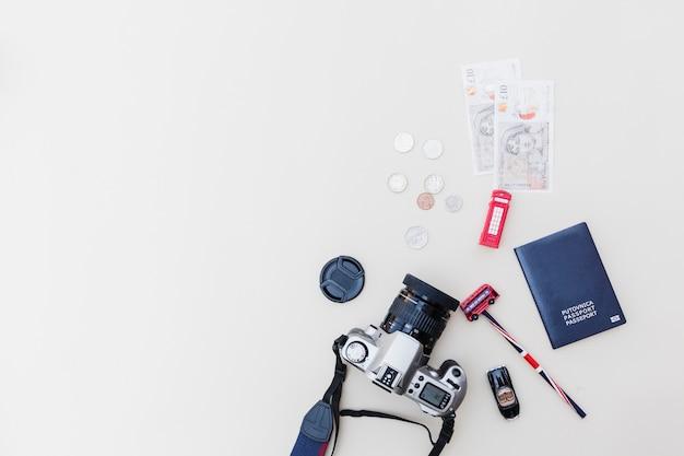Vista elevada de la cámara dslr, pasaporte, monedas y juguetes sobre fondo brillante