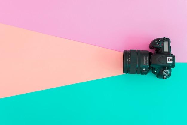 Vista elevada de cámara profesional sobre fondo coloreado.