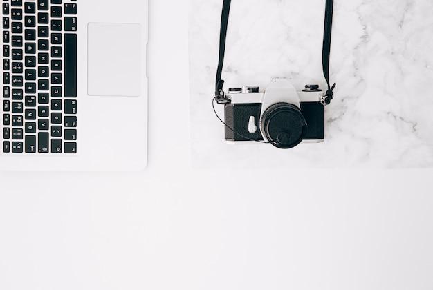 Una vista elevada de la cámara vintage y la computadora portátil en el escritorio blanco