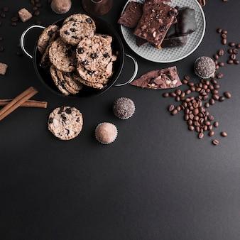 Una vista elevada de la canela; galletas; trufas de chocolate y granos de café sobre fondo negro