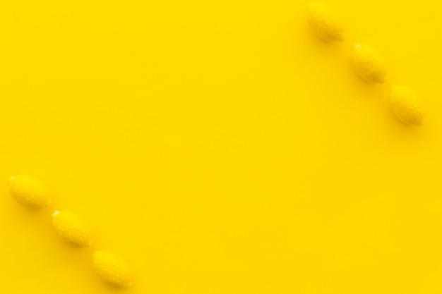 Vista elevada de caramelos de limón sobre fondo amarillo