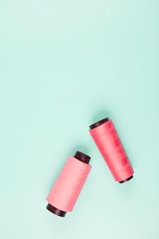 Una vista elevada de carretes de color rosa y coral sobre fondo de menta