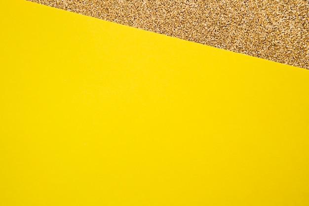 Vista elevada de cartulina amarilla sobre alfombra dorada