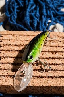 Una vista elevada de cebo de pesca verde en tablero de corcho