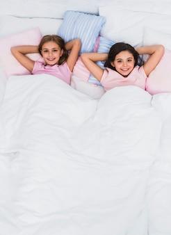 Una vista elevada de chicas sonrientes acostado en la cama mirando a la cámara