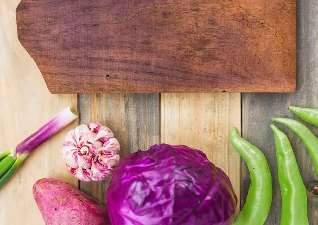 Vista elevada de chiles verdes; ajo; repollo; patata dulce y tabla para picar sobre fondo de madera