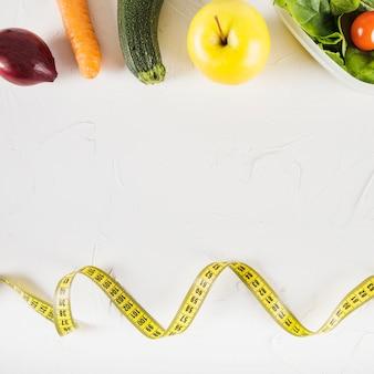 Vista elevada de cinta métrica y comida sana sobre fondo blanco