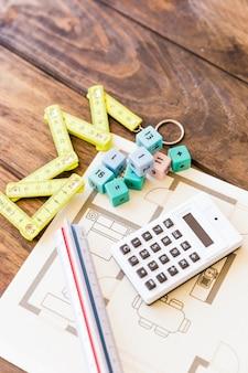 Vista elevada de cinta métrica, regla, calculadora, bloques matemáticos y planos