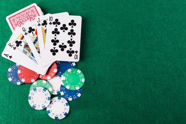 Vista elevada de los clubes y fichas de la escalera real en la mesa de póquer verde