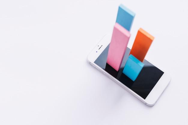 Vista elevada de coloridas barras saliendo de la pantalla del teléfono móvil