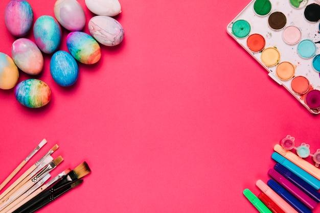 Una vista elevada de coloridos huevos de pascua; cepillos rotulador y caja de pintura de acuarela sobre fondo rosa