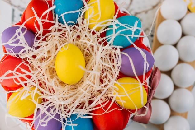 Una vista elevada de coloridos huevos de pascua en papel triturado