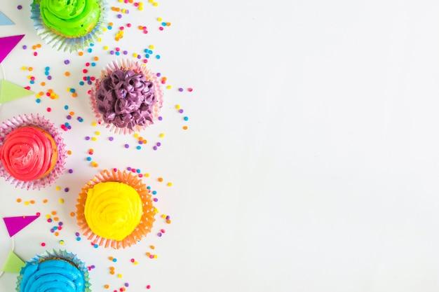 Vista elevada de coloridos muffins y bunting en superficie blanca