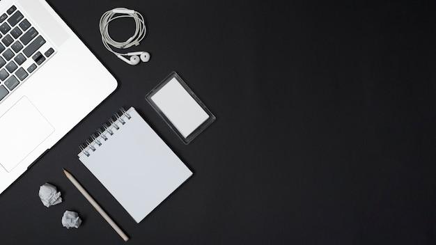 Vista elevada de la computadora portátil; auriculares; papeles arrugados; lápiz; bloc de notas de espiral en blanco y marco sobre fondo negro