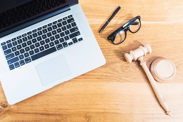 Vista elevada de la computadora portátil; gafas; martillo y pluma sobre fondo de madera