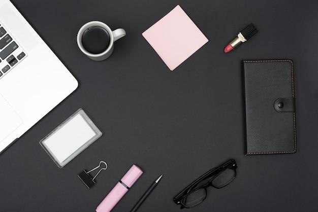 Vista elevada de la computadora portátil; lápiz labial; taza de café y material de oficina sobre fondo negro