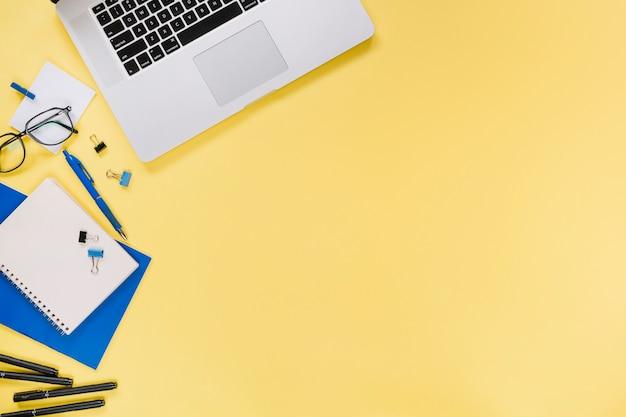 Vista elevada de la computadora portátil y papelería sobre fondo amarillo