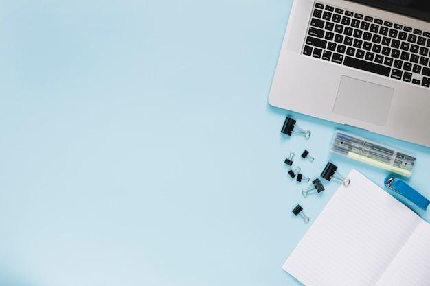 Vista elevada de la computadora portátil y papelería sobre fondo azul