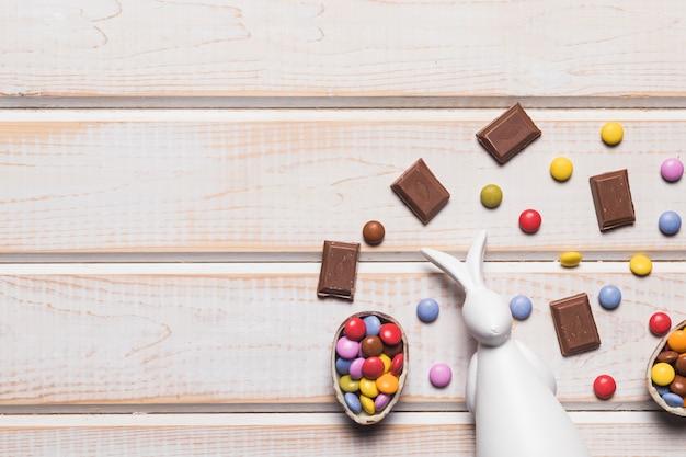 Una vista elevada del conejito blanco con caramelos de gemas y trozos de chocolate en un tablón de madera