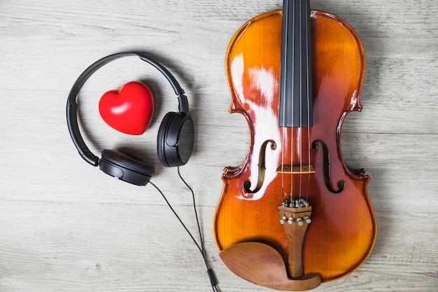 Vista elevada del corazón rojo rodeado de auriculares y guitarra clásica de madera en la mesa gris