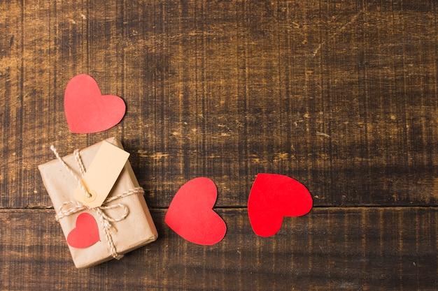 Vista elevada de corazones; caja de regalo y etiqueta en el panel de textura
