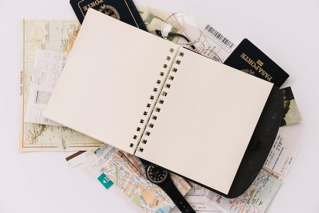 Vista elevada del cuaderno espiral en blanco en los pasaportes y mapas sobre fondo blanco