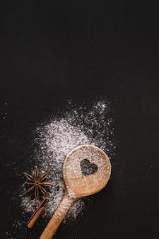 Vista elevada de la cuchara en forma de corazón; especias y harina sobre fondo negro