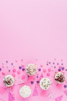 Vista elevada de cupcakes; caramelos y bunting en superficie rosa