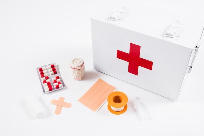 Vista elevada de botiquín de primeros auxilios con equipos médicos sobre fondo blanco