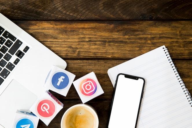 Vista elevada de café, bloc de notas con gadgets electrónicos e iconos de medios