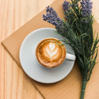 Vista elevada de café con leche, cuaderno y flor de lavanda