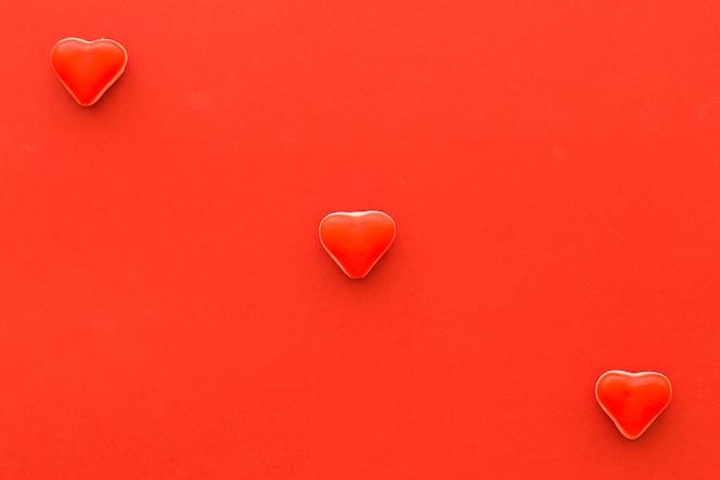 Vista elevada de caramelos de forma de corazón sobre fondo rojo