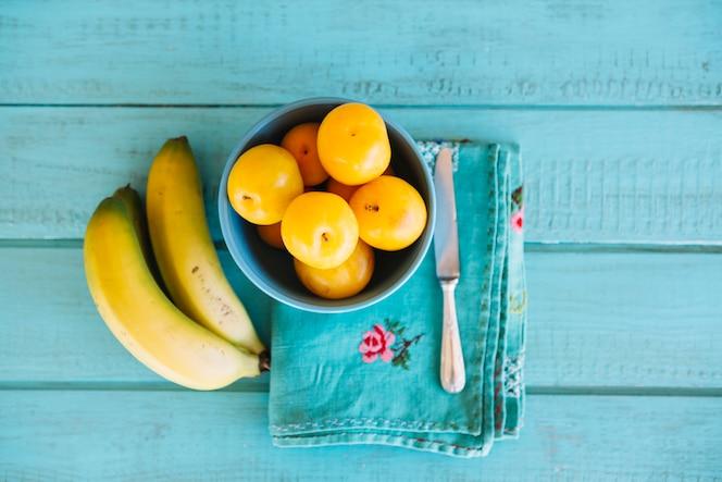 Vista elevada de ciruelas y plátanos en el escritorio de madera azul