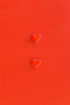 Vista elevada de dos caramelos en forma de corazón sobre fondo rojo