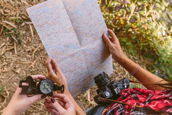 Vista elevada de dos mujeres con brújula y mapa